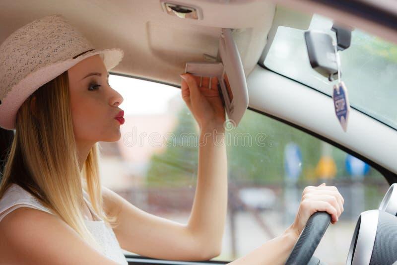 Femme distraite conduisant sa voiture regardant dans le miroir photos stock