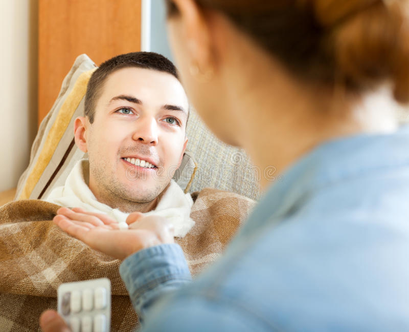 Femme donnant l'homme de pilules image stock