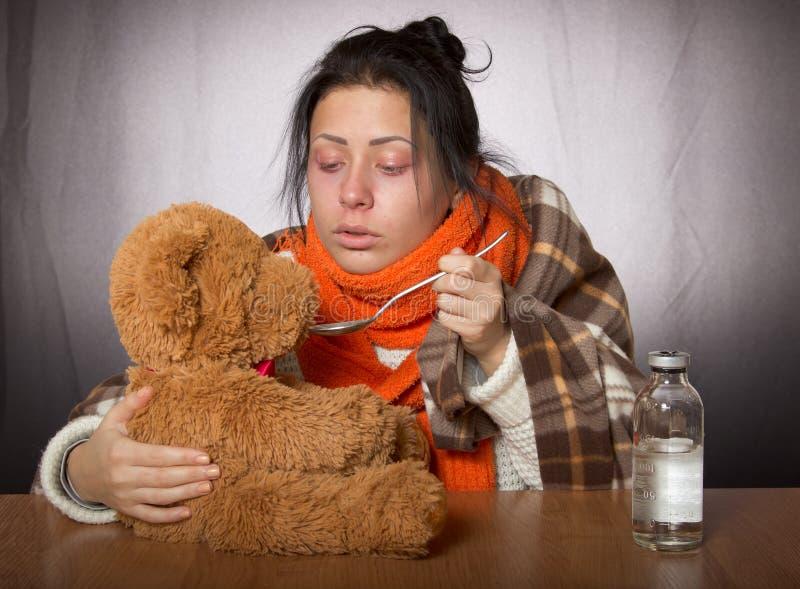 Femme donnant l'ours de médecine contre la grippe image stock