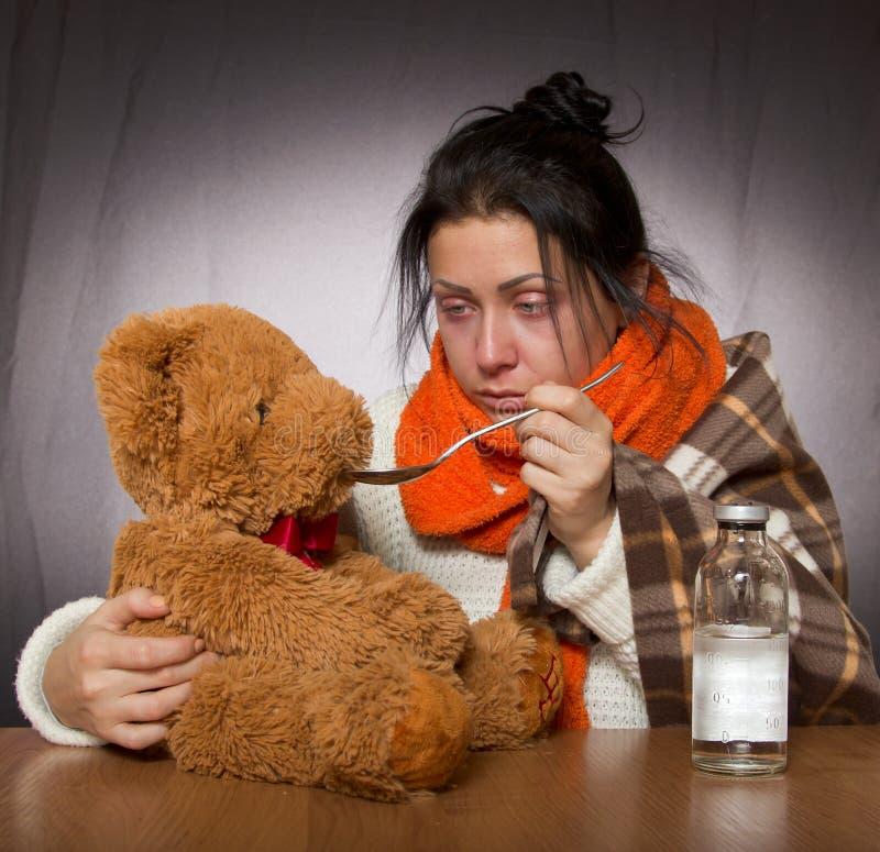 Femme donnant l'ours de médecine contre la grippe image libre de droits