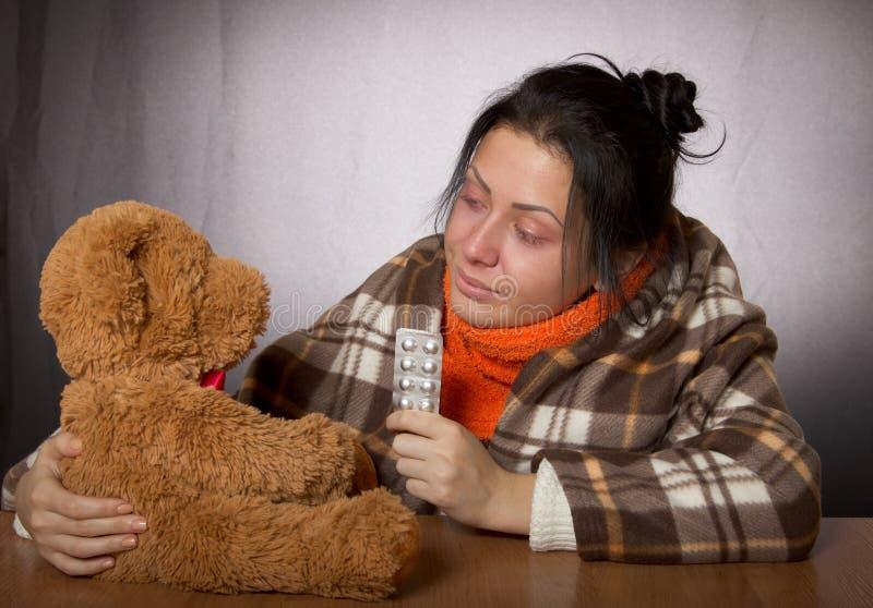 Femme donnant l'ours de médecine contre la grippe photos stock