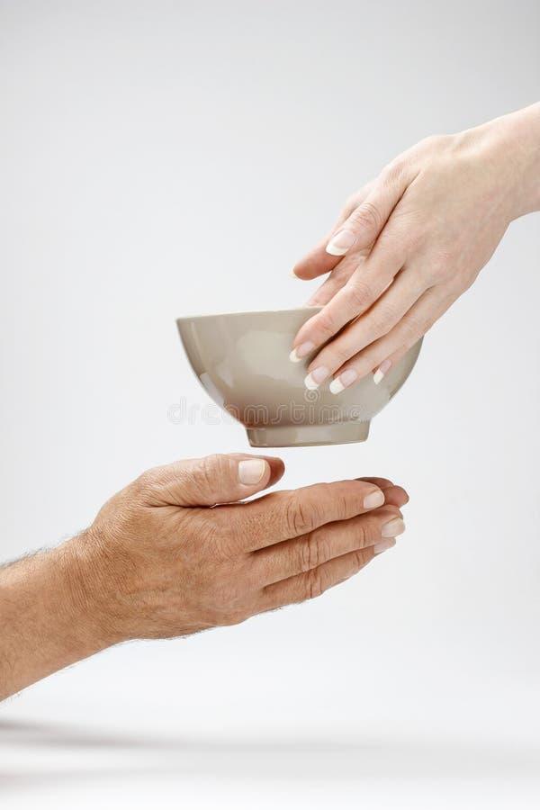 Femme donnant la cuvette de repas chaud à l'homme affamé image stock