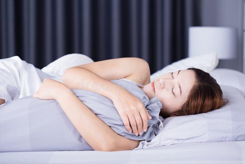 Femme dormant avec l'oreiller de traversin sur le lit dans la chambre à coucher images stock