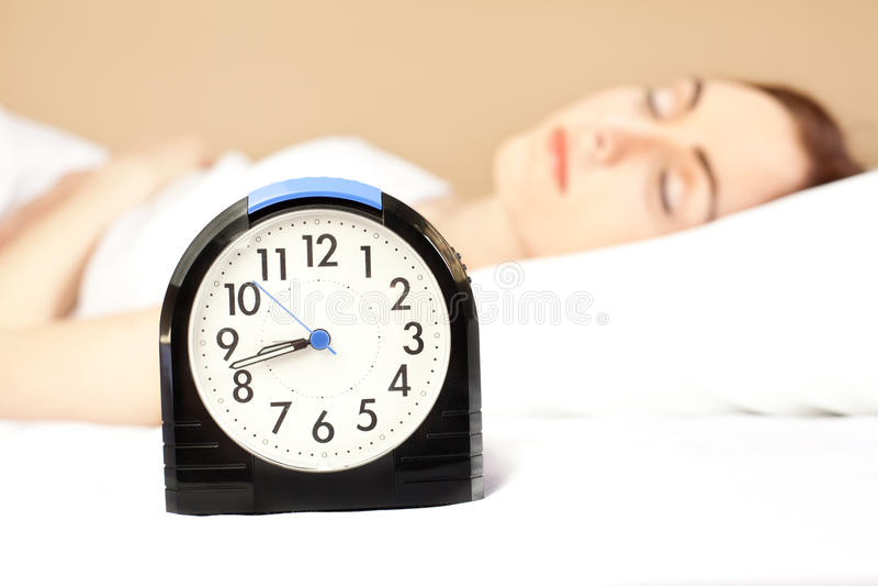 Femme Dormant Dans Le Bâti (orientation Sur L Horloge D Alarme) Photos libres de droits