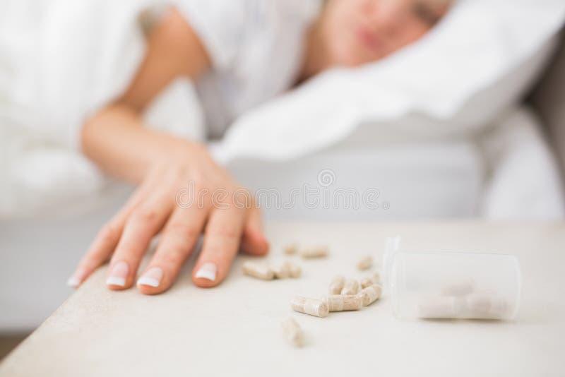 Femme dormant dans le lit avec des pilules dans le premier plan photos libres de droits