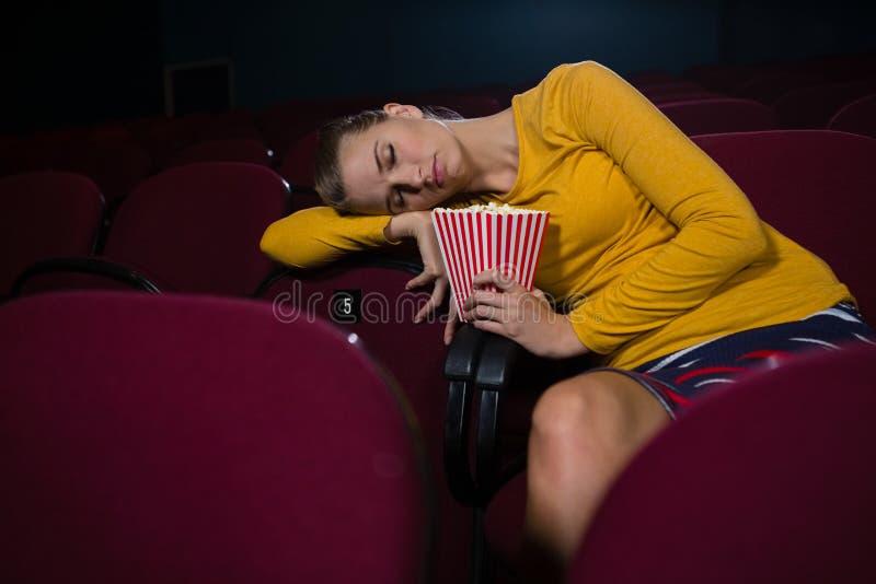 Femme dormant dans un théâtre de film image stock