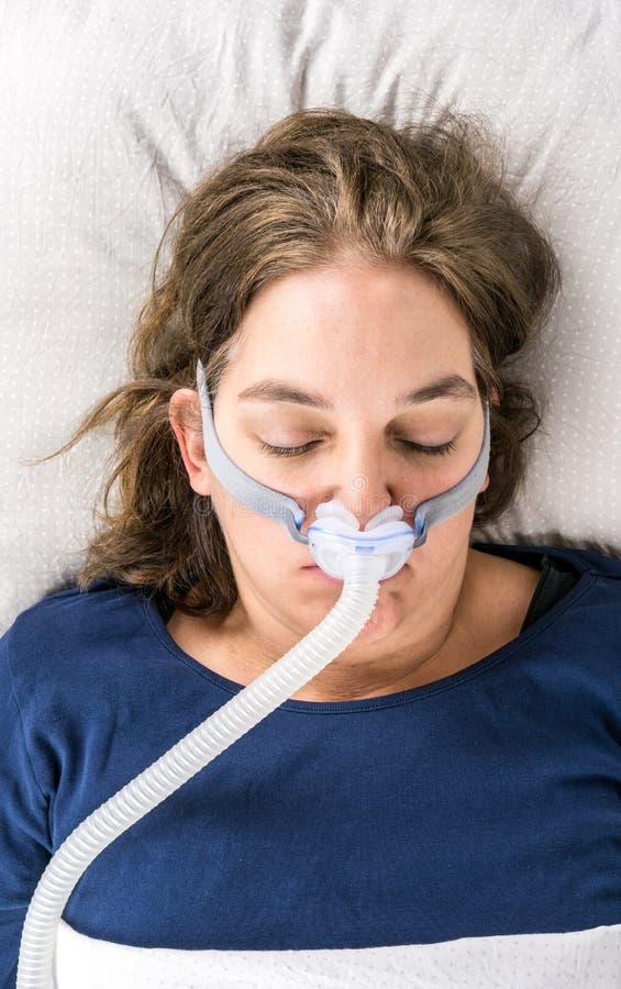 Femme dormant sur elle de retour avec CPAP, traitement d'apnée du sommeil image libre de droits