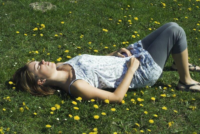 Femme dormant sur l'herbe photo stock