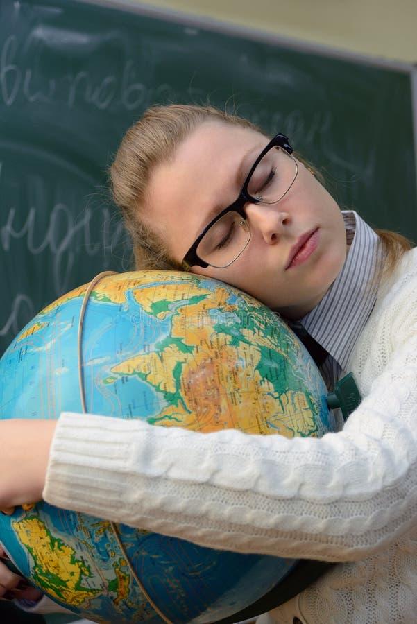 Femme dormant sur le globe image stock