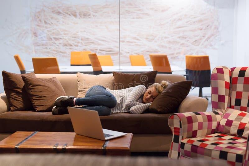 Femme dormant sur un sofa dans un bureau créatif photo stock
