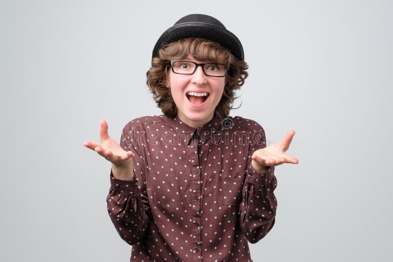 Femme drôle caucasienne dans les lunettes et le chapeau excité par les nouvelles photographie stock
