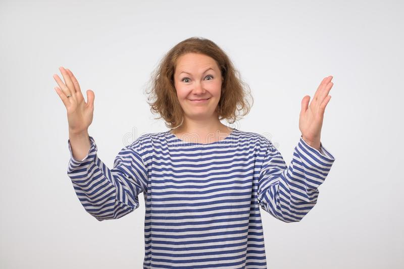 Femme drôle dans la chemise rayée montrant quelque chose grande dans la taille avec des mains images stock