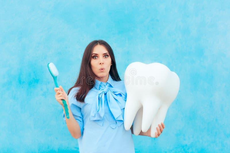 Femme drôle tenant la dent surdimensionnée dans le dentiste Concept Image photographie stock libre de droits
