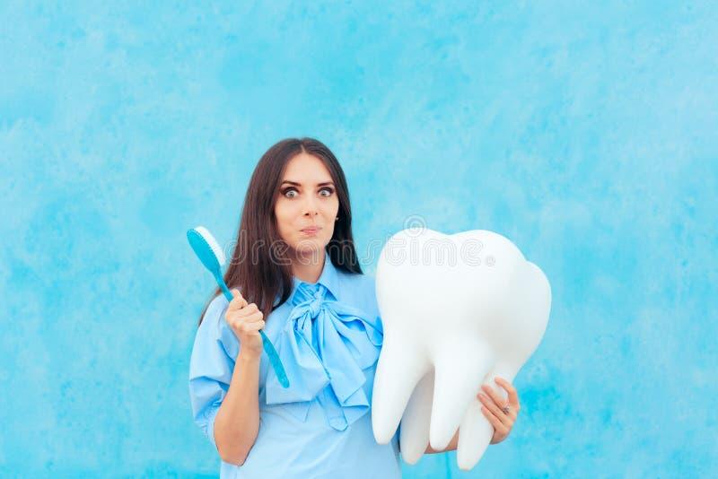 Femme drôle tenant la dent surdimensionnée dans le dentiste Concept Image images stock