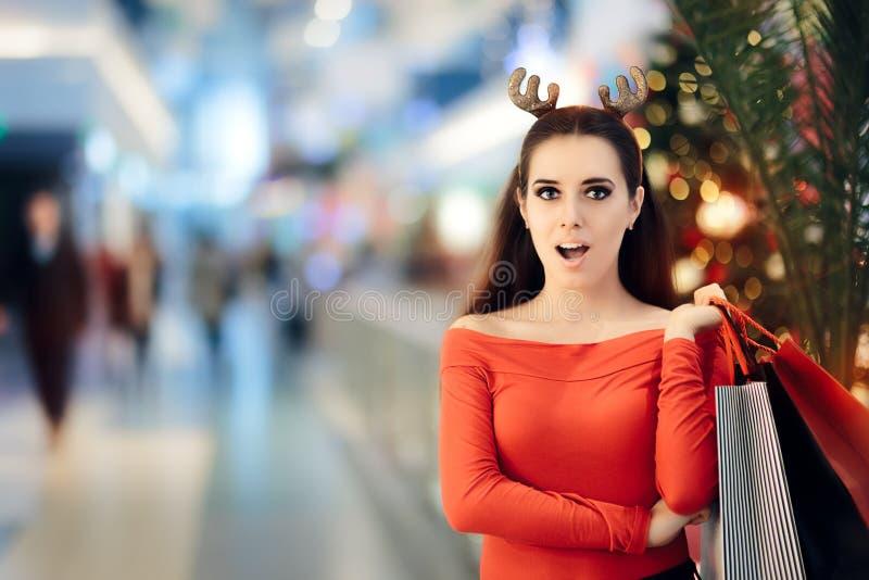 Femme drôle avec des achats de bandeau de klaxons de renne de Noël images stock