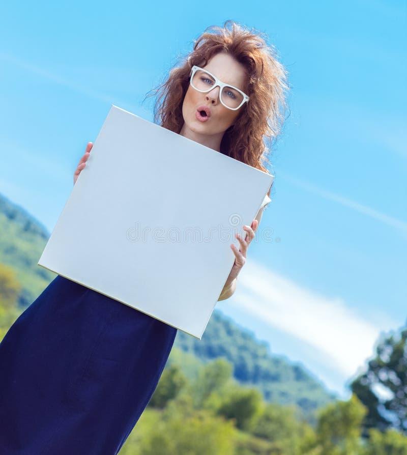 Femme drôle expressive tenant le conseil blanc photographie stock libre de droits