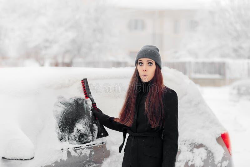 Femme drôle une brosse étant coupé la neige de la voiture image libre de droits
