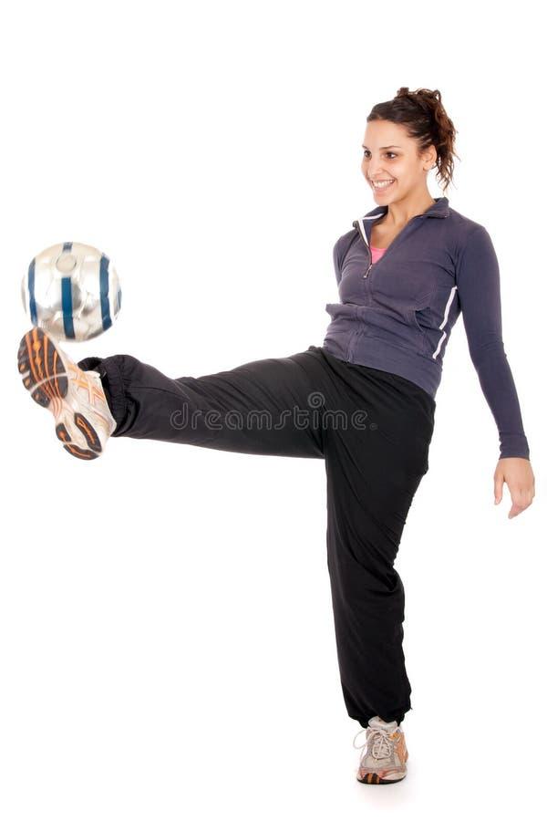 Femme du football donnant un coup de pied la bille photographie stock