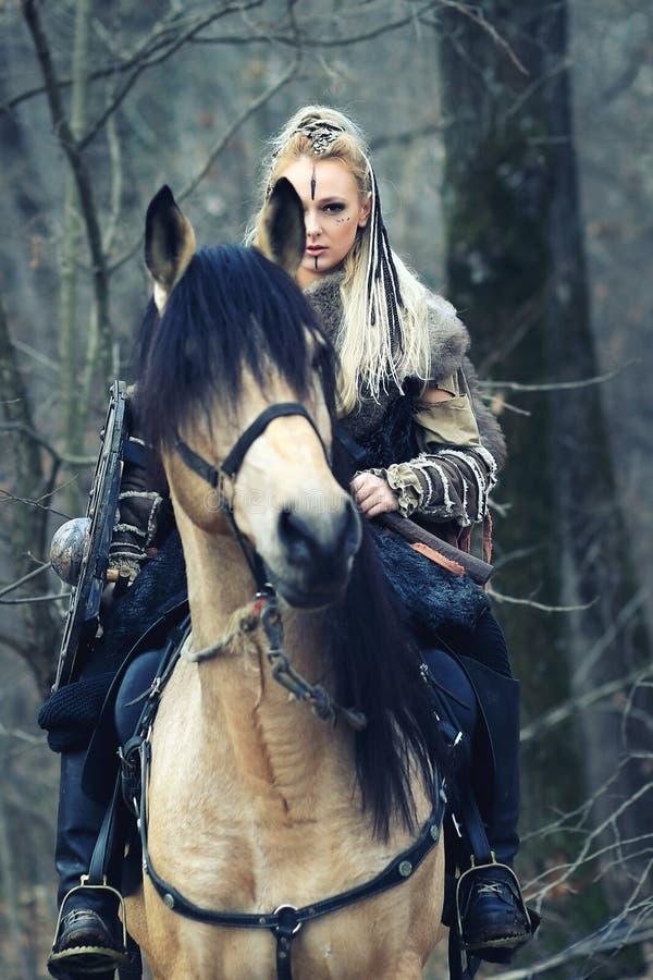 Femme du nord extérieure de guerrier avec bouclier et hache tressés de participation de maquillage de cheveux et de guerre avec l images libres de droits