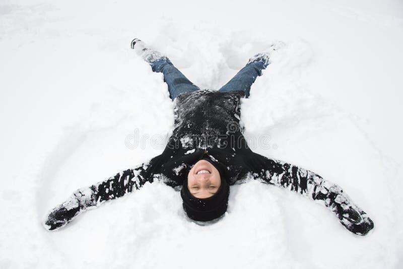 Femme effectuant l'ange de neige. photos libres de droits