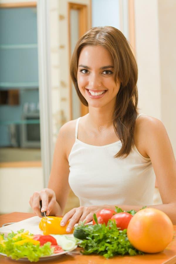Femme effectuant la salade à la cuisine image libre de droits