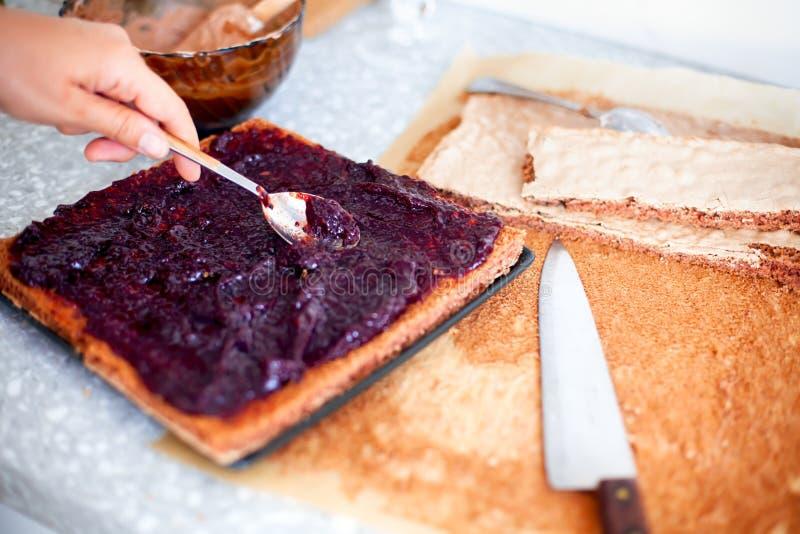 Femme effectuant le g?teau La main de personne avec la cuillère répand la confiture sur le gâteau mousseline image libre de droits