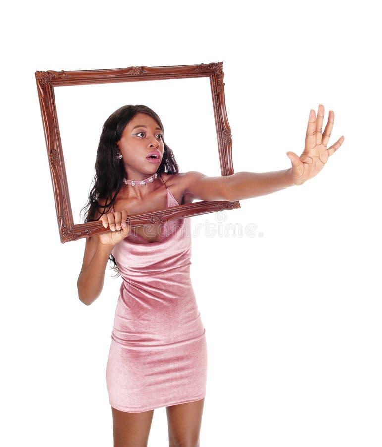 Femme effrayée atteignant cependant le cadre photo stock
