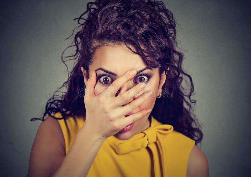 Femme effrayée couvrant son visage de mains jetant un coup d'oeil par des doigts photographie stock libre de droits