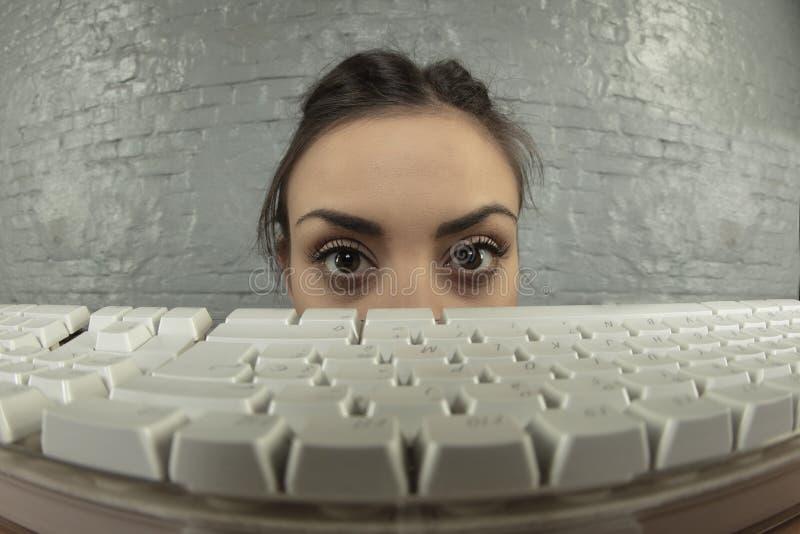 Femme effrayée d'affaires, yeux collant au-dessus du clavier images stock