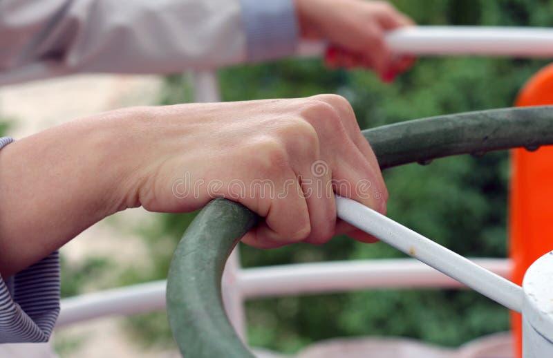 Femme effrayée de la taille de la grande roue se tenant fermement dessus sur les balustrades de l'oscillation photo stock