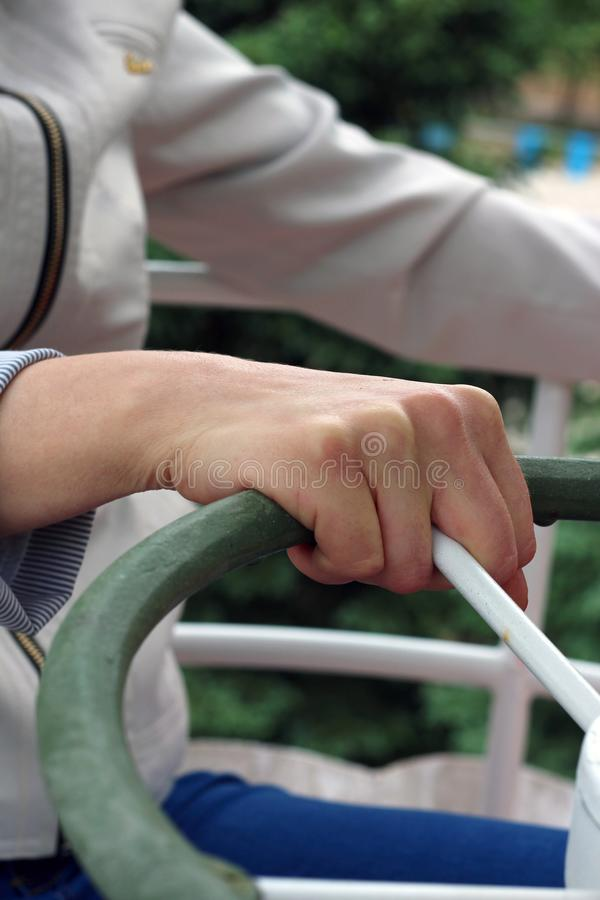 Femme effrayée de la taille de la grande roue se tenant fermement dessus sur les balustrades de l'oscillation images libres de droits