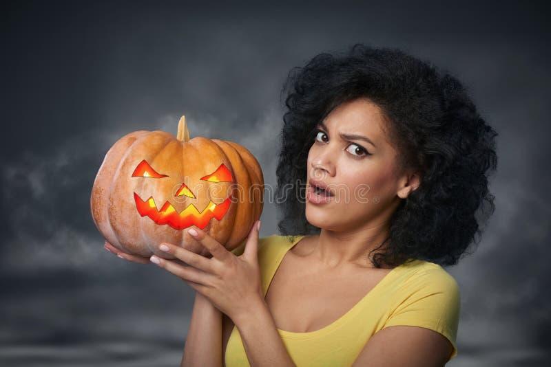 Femme effrayée tenant le potiron de Halloween photos stock