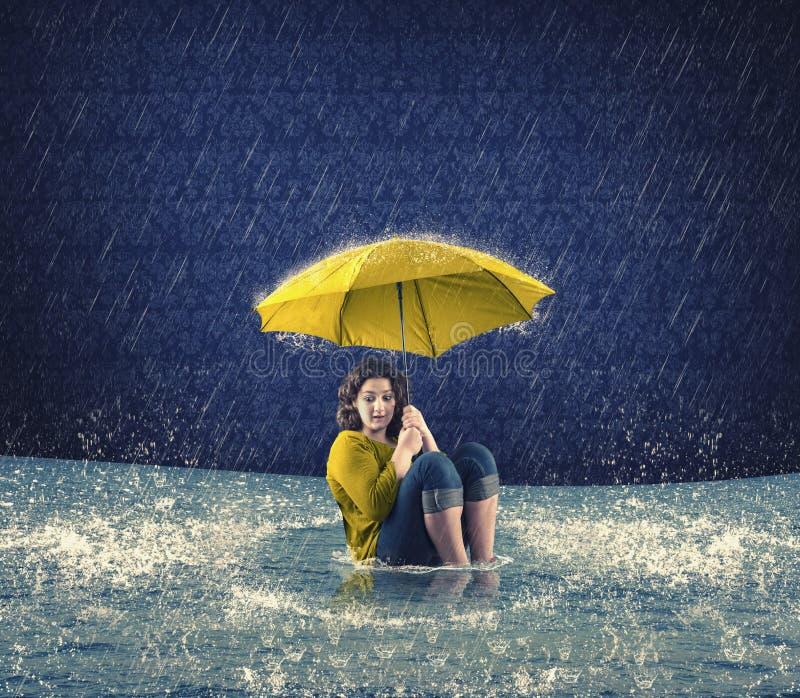 Femme effrayée tenant un parapluie tandis qu'il pleuvant photos libres de droits