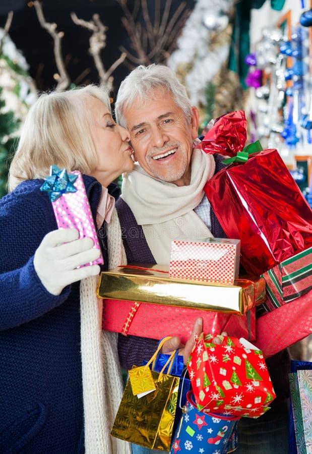 Femme embrassant l'homme au magasin de Noël photo stock