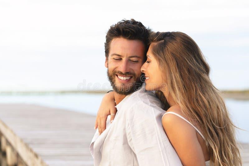 Femme embrassant son homme par derrière sur le fond de bord de la mer images libres de droits