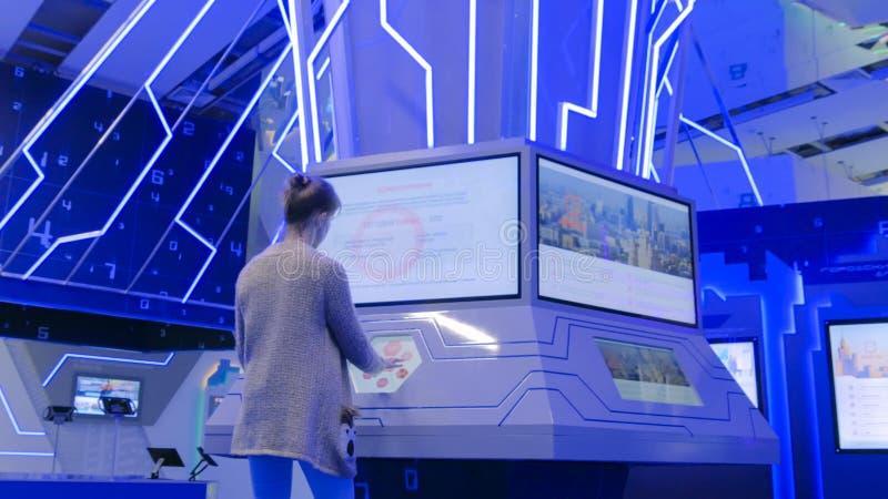 Femme employant l'affichage interactif d'écran tactile à l'exposition urbaine photographie stock