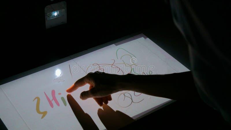 Femme employant l'affichage interactif de projecteur d'écran tactile pour le dessin photographie stock libre de droits