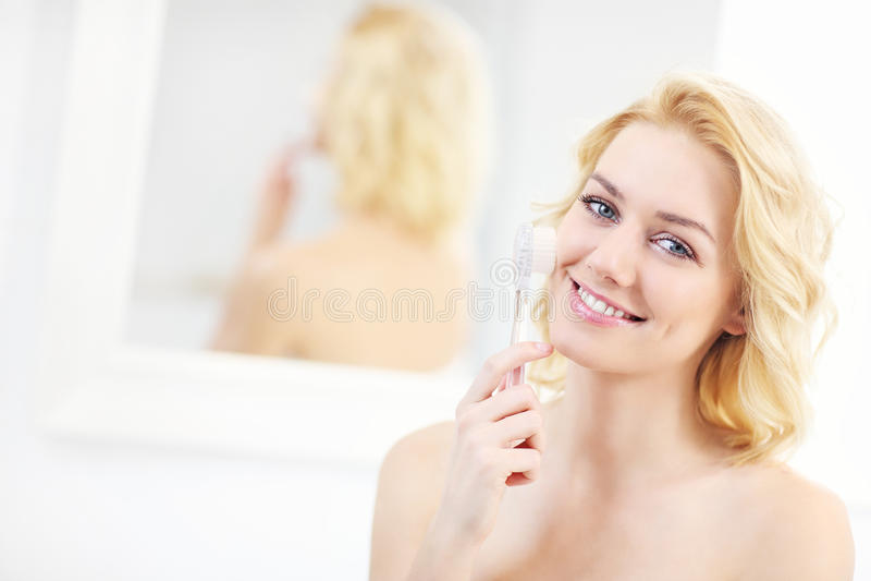 Femme employant la brosse de nettoyage de visage images stock