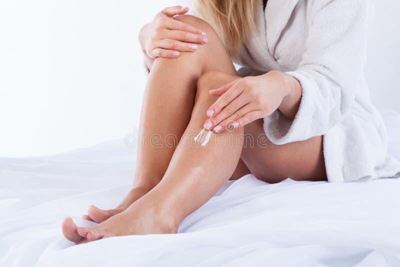 Femme employant la crème corporelle photo stock