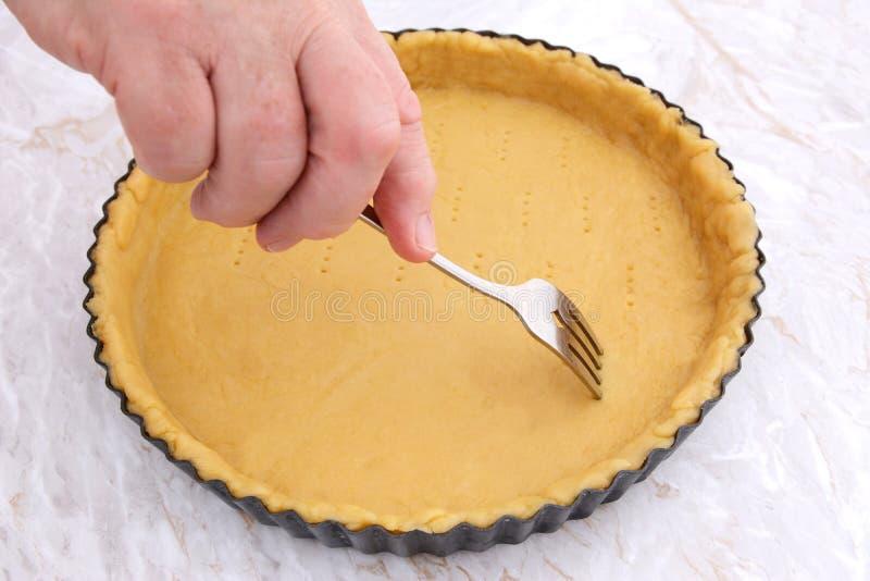 Femme employant la fourchette pour piquer des trous dans une pâte à tarte crue images libres de droits