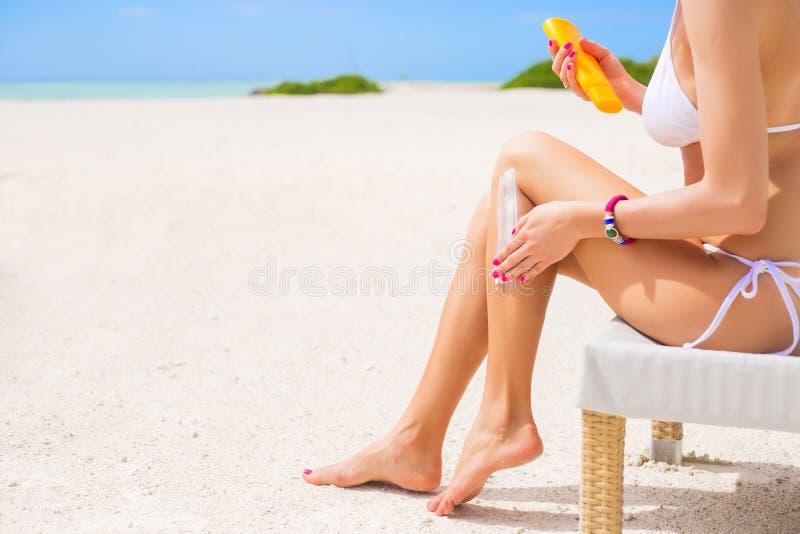 Femme employant la protection solaire sur la plage photo libre de droits