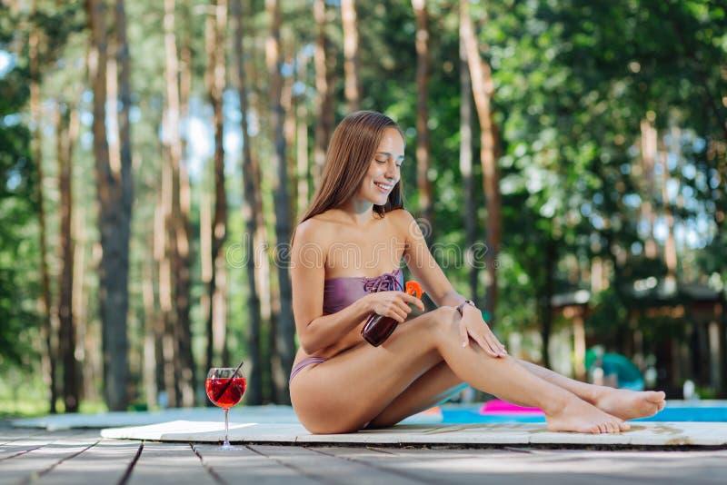 Femme employant la séance crème de protection du soleil près de la piscine extérieure photos stock