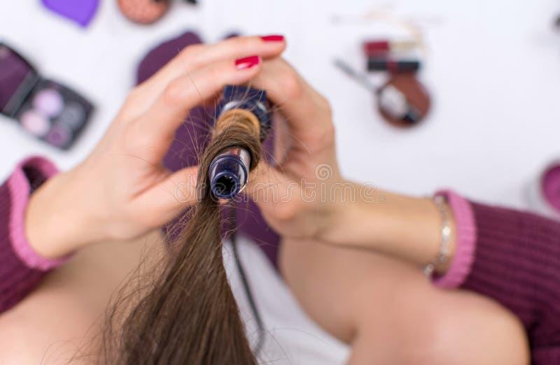 Femme employant le fer de bordage sur ses cheveux photographie stock