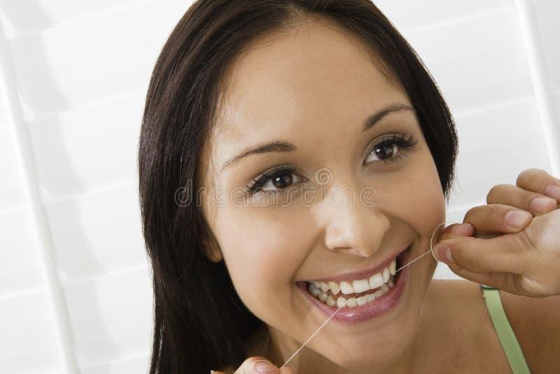 Femme employant le fil dentaire photos stock