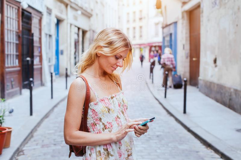 Femme employant le mobile sur la rue, téléphone intelligent APP photos libres de droits