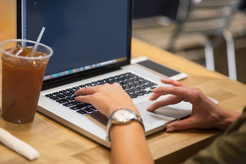 Femme employant le réseau de wifi en café sur l'ordinateur portable image stock