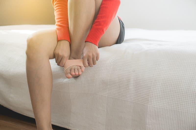 Femme employant le silicone de soutien pour le fasciitis plantaire de traitement sur son pied photos libres de droits