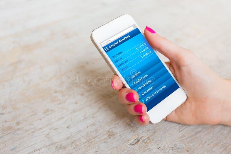 Femme employant le site Web d'opérations bancaires en ligne sur le smartphone photo stock