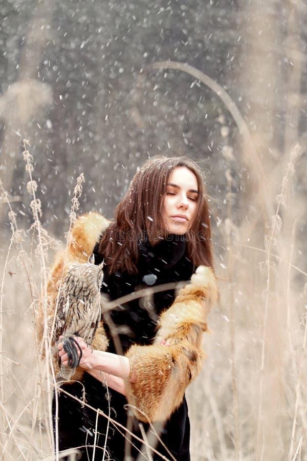 Femme en automne dans le manteau de fourrure avec la première neige de hibou en main Beautif image stock