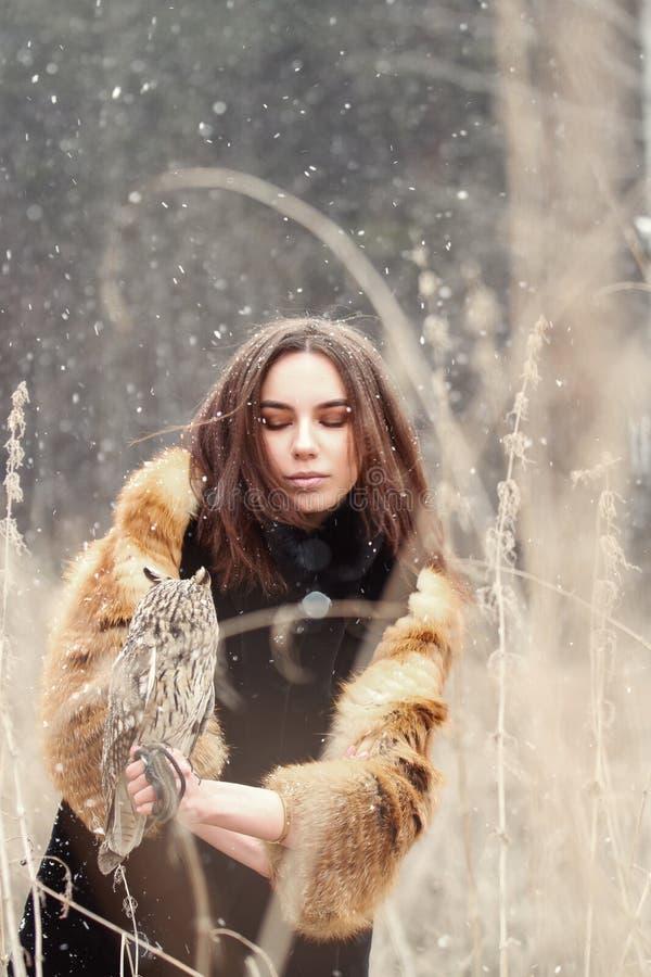 Femme en automne dans le manteau de fourrure avec la première neige de hibou en main Belle fille de brune avec de longs cheveux e photos stock